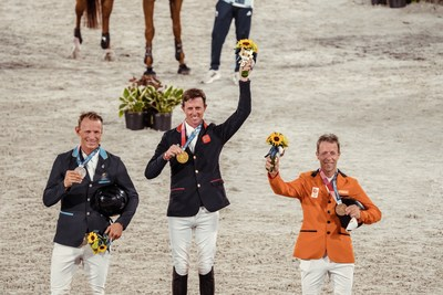 Great Britain's Ben Maher celebrates his gold medal win in the Individual Showjumping Final at the Tokyo 2020 Olympic Games at the Baji Koen Equestrian Park. L to R: Peder Fredricson (SWE), Ben Maher (GBR), Maikel van der Vleuten (NED) (FEI/Christophe Taniere)